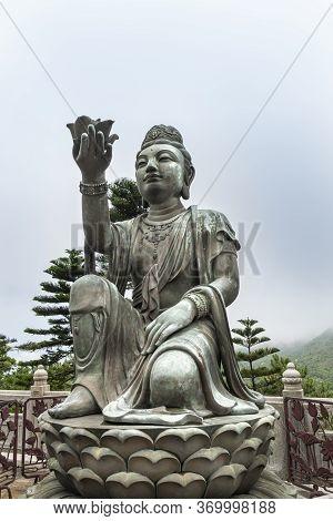 Buddhist Deva Statue Offering A Flower To The Tian Tan Big Buddha  Statue On Lantau Island, Hong Kon