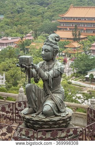 Buddhist Deva Statue Offering Incense To The Tian Tan Big Buddha  Statue On Lantau Island, Hong Kong