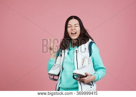 Figure Skating, Hobbies And A Healthy Active Lifestyle. A Cheerful Girl In A Bright Hoodie With Skat