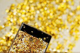Photo Of Golden Confetti On A Smartphone Screen.