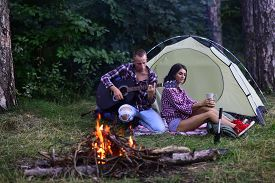 Young Couple Of Tourists Together. Couple In Love Sitting Near Touristic Tent In Forest. Couple In L
