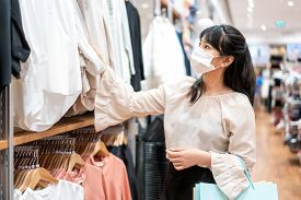 Asian Woman Wearing Mask Over Her Face While Choosing Shirt At Shopping Mall With Shopping Bag For H