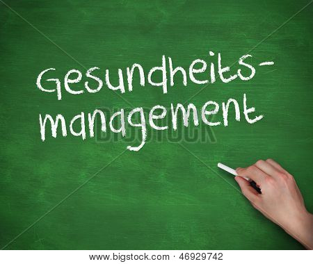Hand writing gesundheits management on a green board