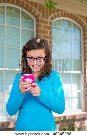 Tiener meisje met glazen spelen met roze smartphone lachend