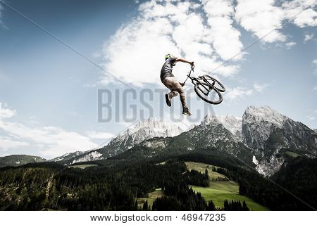 stunt biker jumps over mountain