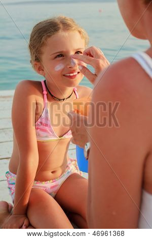 Sun protection. Mother anoints her daughter face protective cream on the beach poster