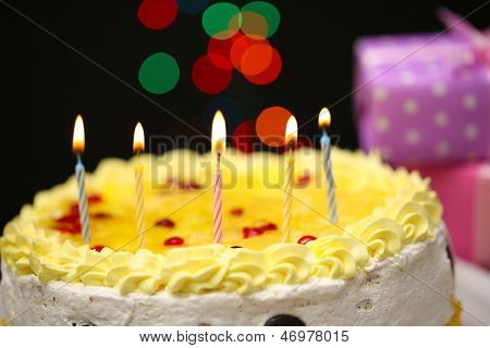 Happy birthday cake and gifts, on black background