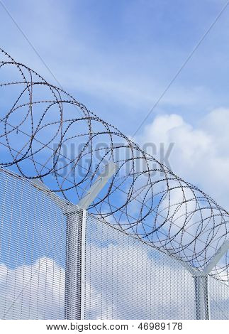 Chain link fence with barbed wire under blue sky