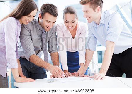 Coworkers leaning over table in office