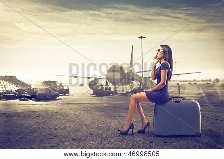 beautiful woman waits sitting on suitcase talking on the phone to start