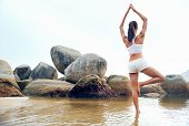 yoga beach woman doing pose at the ocean for zen health and peaceful lifestyle poster