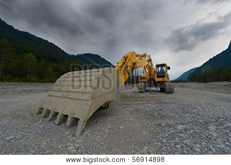 orange mechanical shovel excavator or bucket digger on gravel