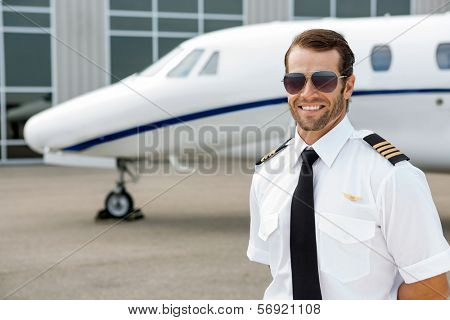 Confident pilot smiling in front of private jet poster