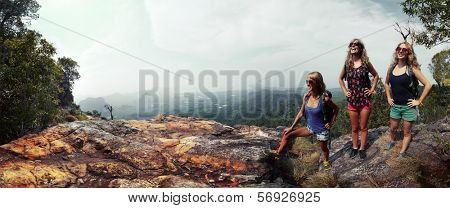 Three happy ladies with backpacks standing on top of a mountain and enjoying valley view