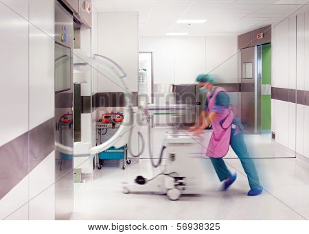 Blurred doctor or nurse with protective uniform is pushing C-arm x-ray into surgery.