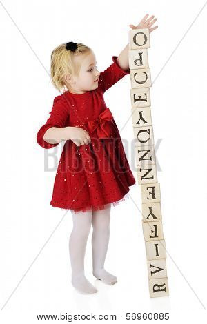 An adorable and dressed up preschooler creating a tower out of alphabet blocks.  The tower is about ready to topple.  On a white background.