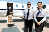 Portrait of confident stewardess and pilot standing against private jet poster