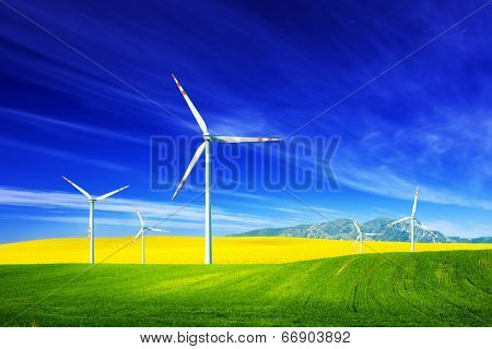 Wind turbines on spring field. Alternative, clean and natural source of energy is gaining pupularity. Eco farm.