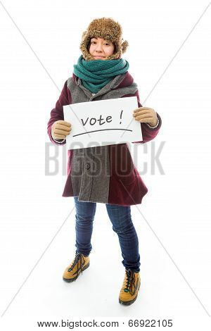 Young woman in warm clothing and showing vote sign on white back