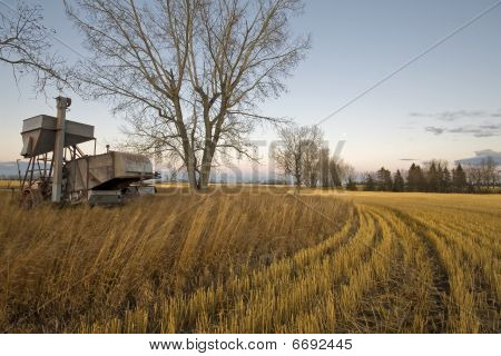 Field At Sunset With Rusting Farm Equipment