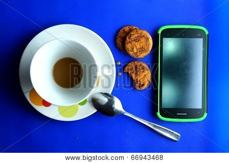 Finished Coffee in a ceramic cup, cookies and a cellphone