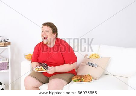 Lazy overweight male sitting with fast food on couch and watching television poster