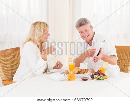 Mature Couple Using And Pointing At A Tablet Computer While Enjoying Their Healthy Breakfast