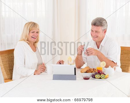 Mature Couple Laughing And Video Chatting With A Tablet As They Eat Healty Breakfast
