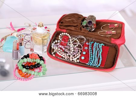 Handbag with accessorises and perfumes in bottles on table on  home interior background