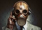 Man wearing vintage gas mask and headphones listening to music. poster