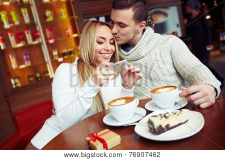 Young couple sitting in caf���© and watching photos