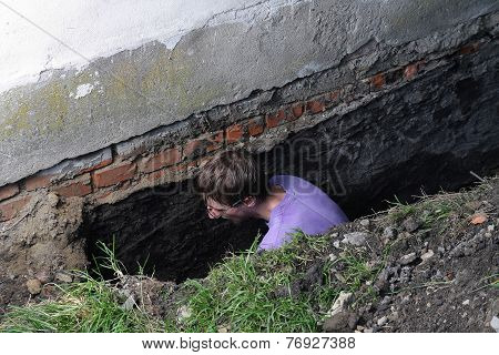 Young man preparing hole in ground for Installation of new studded film as insulation against ground