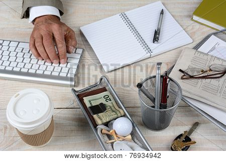 Closeup of a businessman's desk. The white rustic wood desk has a keyboard, coffee cup, keys, notebook, glasses, pencil cup, newspaper money and golf ball and tee, High angle shot with the man typing.