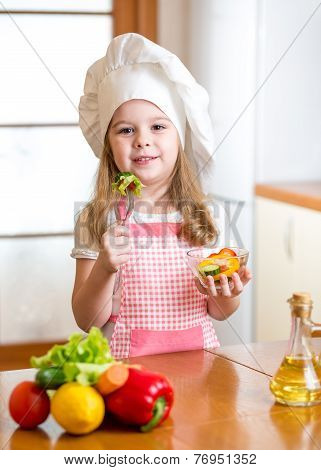 child girl in cook hat eating vegetables