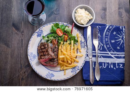 Steak Dinner With Fries And Sauce On The Side