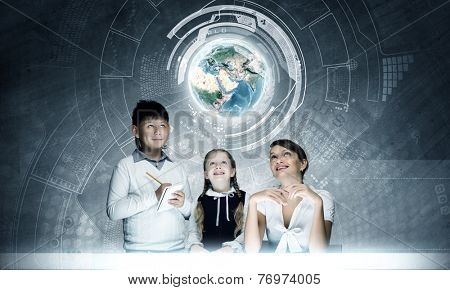 Young teacher and school children examining hologram. Elements of this image are furnished by NASA