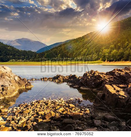 Lake Shore With Stones Near Pine Forest On Mountain At Sunset