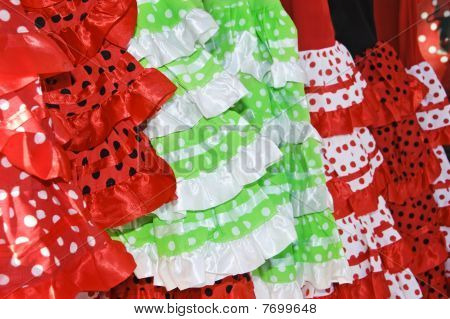 a pile of different flamenco dresses typical of Spain poster