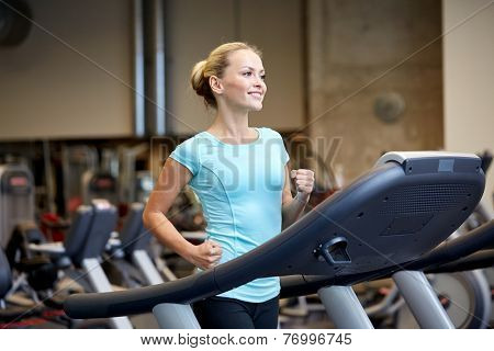 sport, fitness, lifestyle, technology and people concept - smiling woman exercising on treadmill in gym poster