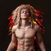 Naked indian strong man with traditional native american make up and headdress. Mixed light  studio shot poster