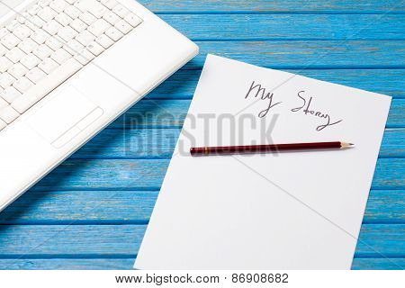 pencil and paper with My Story words near notebook on blue wooden table poster