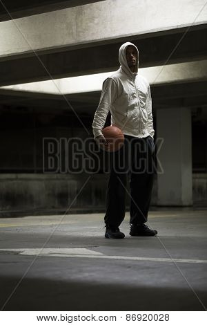 Hooded basketball player looks to camera