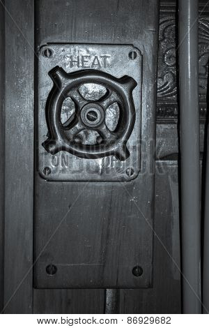 Old fashioned heating switch off, on switch or knob retro image close up on panelled wall.