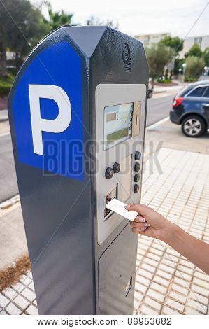 Hand Is Slipping Curd Into Parking Meter