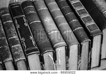 Old Books With Leather Covers Lay On The Shelf