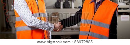 Workers In Factory Shake Hands