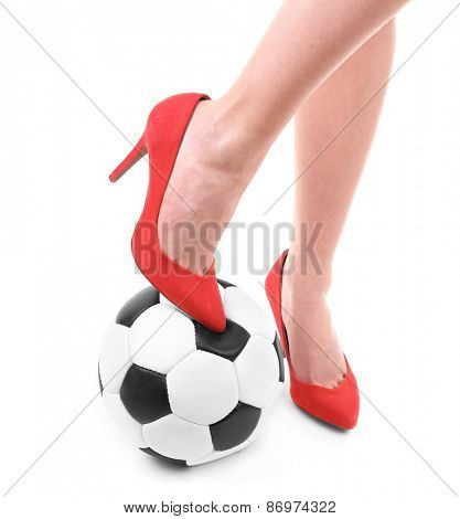 Female legs in red high heeled shoes with soccer ball isolated on white