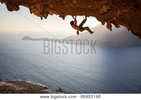 Rock climber climbing along roof in cave at sunset