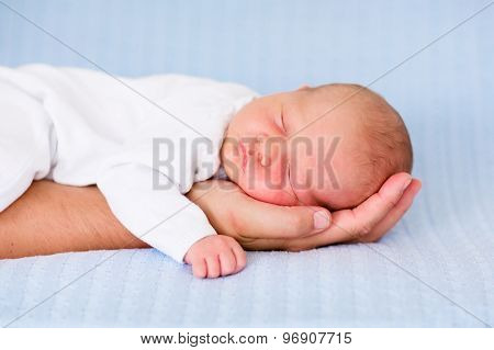 Newborn Baby Boy Sleeping On The Hand Of His Father