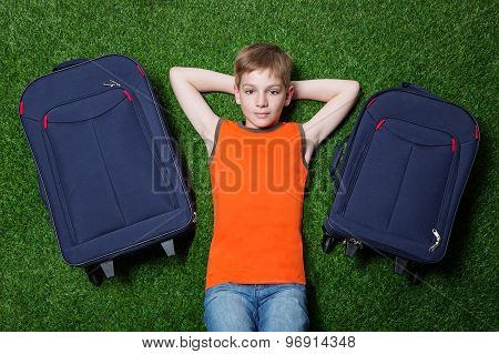 Boy with siutcases th lying on green grass